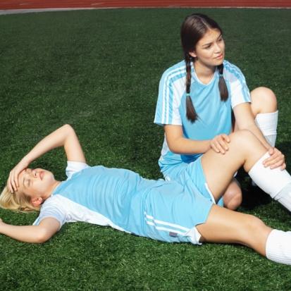 Soccer_player_holding_teammates_injured_leg_0